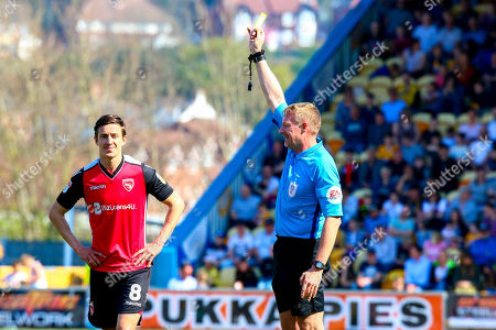 Andrew Fleming of Morecambe is shown the yellow card