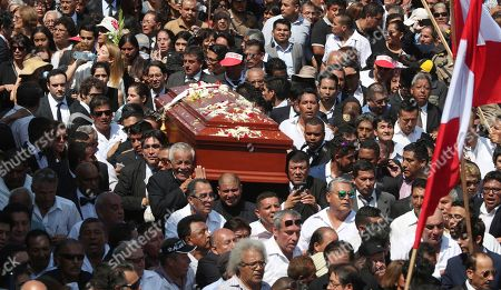 People carry the coffin of Peru's late President Alan Garcia during his funeral procession in Lima, Peru, . Garcia shot himself in the head and died Wednesday as officers waited to arrest him in a massive graft probe that has put the country's most prominent politicians behind bars and provoked a reckoning over corruption