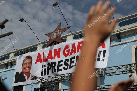 "A supporter waves his hand in front of photo of Peru's late President Alan Garcia that reads in Spanish ""Present!"" during his funeral procession in Lima, Peru, . Garcia shot himself in the head and died Wednesday as officers waited to arrest him in a massive graft probe that has put the country's most prominent politicians behind bars and provoked a reckoning over corruption"