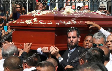Alan Raul Garcia, son of Peru's late President Alan Garcia, carries the coffin of his father during the funeral procession in Lima, Peru, . Garcia shot himself in the head and died Wednesday as officers waited to arrest him in a massive graft probe that has put the country's most prominent politicians behind bars and provoked a reckoning over corruption