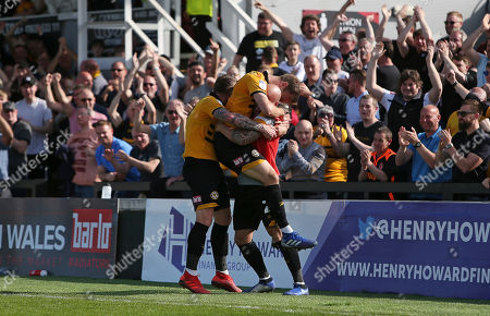 Mickey Demetriou of Newport County celebrates scoring a goal with David Pipe and team mates.