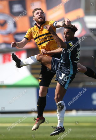 Mark O'Brien of Newport County and Nicky Maynard of Bury go up for the ball.