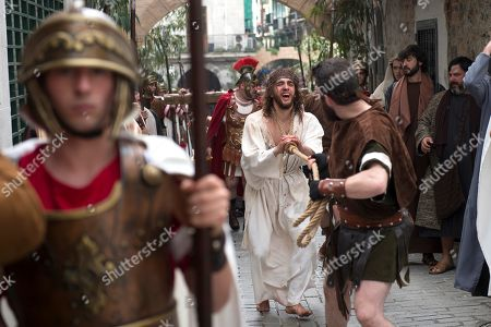 Stock Image of Spanish Christians re-enact the crucifixion of Jesus Christ during the Good Friday in Castro Urdiales village, Cantabria, northern Spain, 19 April 2019. The Good Friday is one of the highest religious holidays observed by Christians all over the world, commemorating the crucifixion of Jesus Christ and his death at Golgotha, a central event in Christian theology.