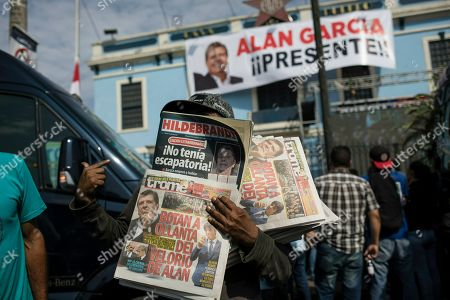 A newspaper vendor works outside the political party headquarters of Peru's late President Alan Garcia as his wake is held in Lima, Peru, early . Garcia shot himself in the head and died Wednesday as officers waited to arrest him in a massive graft probe that has put the country's most prominent politicians behind bars and provoked a reckoning over corruption