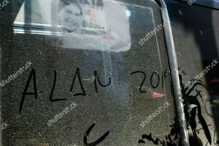 "Words written on a dirty window reads ""Alan 2019"" where a supporter carries a flag with a portrait of Peru's late President Alan Garcia during his funeral procession in Lima, Peru, . Garcia shot himself in the head and died Wednesday as officers waited to arrest him in a massive graft probe that has put the country's most prominent politicians behind bars and provoked a reckoning over corruption"