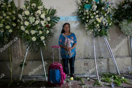 A supporter of Peru's late President Alan Garcia's stands among funeral flowers inside the political party headquarters where his wake is taking place in Lima, Peru, . Garcia shot himself in the head and died Wednesday as officers waited to arrest him in a massive graft probe that has put the country's most prominent politicians behind bars and provoked a reckoning over corruption