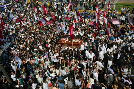 People carry the coffin of Peru's late President Alan Garcia through the street during his funeral procession in Lima, Peru, . Garcia shot himself in the head and died Wednesday as officers waited to arrest him in a massive graft probe that has put the country's most prominent politicians behind bars and provoked a reckoning over corruption