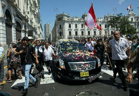 Supporters run next to the hearse carrying Peru's late President Alan Garcia during his funeral procession in Lima, Peru, . Garcia shot himself in the head and died Wednesday as officers waited to arrest him in a massive graft probe that has put the country's most prominent politicians behind bars and provoked a reckoning over corruption