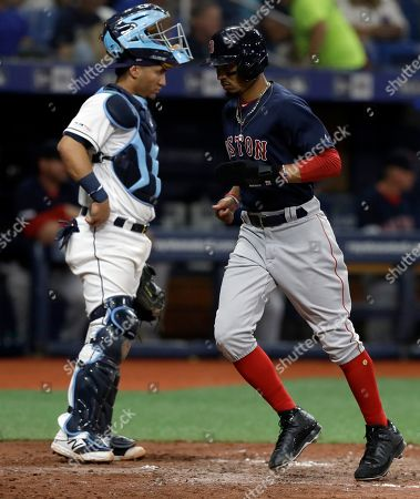 Boston Red Sox's Mookie Betts, right, scores in front of Tampa Bay Rays catcher Michael Perez during the sixth inning of a baseball game, in St. Petersburg, Fla