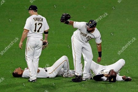 Pittsburgh Pirates' Melky Cabrera, second from right, calls for team trainers, as he and JB Shuck (17) assist center fielder Starling Marte, right, and shortstop Erik Gonzalez, left, lie on the field after colliding while attempting to field a fly ball to short center fielder by San Francisco Giants' Yangervis Solarte in the eighth inning of a baseball game in Pittsburgh, . Solarte was held to a single on the play. Both players were shaken up on the play and left the game, Marte needing to be driven off the field. The Pirates won 4-1