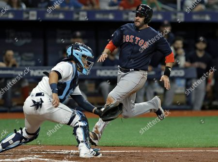 J.D. Martinez, Michael Perez. Boston Red Sox's J.D. Martinez, right, scores around Tampa Bay Rays catcher Michael Perez on an RBI-double by Rafael Devers during the fifth inning of a baseball game, in St. Petersburg, Fla
