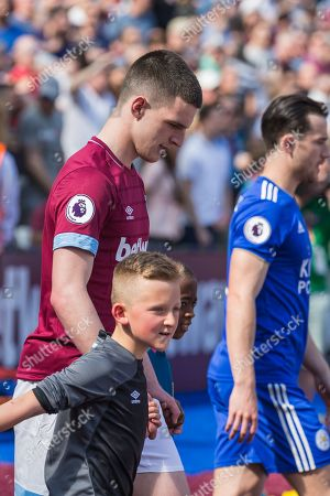 Declan Rice (West Ham) walking onto the pitch with two young supporters during the Premier League match between West Ham United and Leicester City at the London Stadium, London