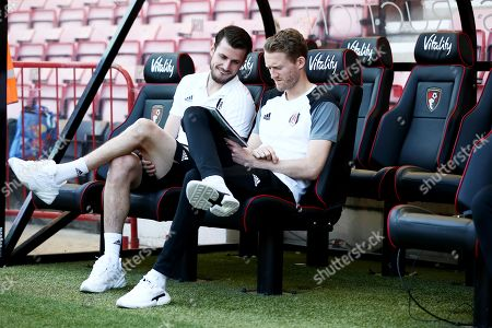 Maxime Le Marchand and Andre Schurrle of Fulham look at the programme.