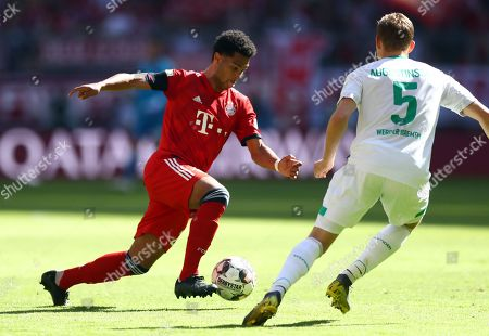 Bayern forward Serge Gnabry fights for the ball with Bremen's defender Ludwig Augustinsson during the German Bundesliga soccer match between Bayern Munich and Werder Bremen at the Allianz Arena in Munich, Germany