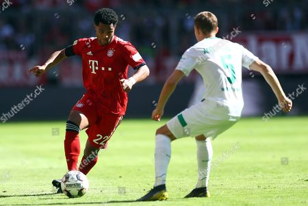 Bayern forward Serge Gnabry, left, fights for the ball with Bremen's defender Ludwig Augustinsson during the German Bundesliga soccer match between Bayern Munich and Werder Bremen at the Allianz Arena in Munich, Germany