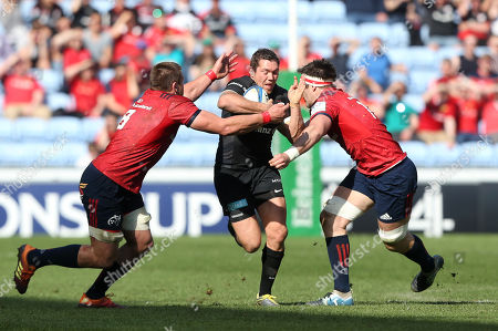 Saracens Alex Goode  is tackled by Munster Rugby's Billy Holland and  CJ Stander