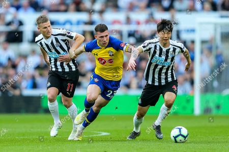 Pierre-Emile Hojbjerg (#23) of Southampton battles to maintain possession of the ball against Ki Sung-Yueng (#4) of Newcastle United and Matt Ritchie (#11) of Newcastle United during the Premier League match between Newcastle United and Southampton at St. James's Park, Newcastle