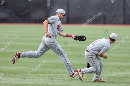 Charleston's Logan McRae, left, catches the ball as Charleston's Luke Manzo, right, ducks during an NCAA college baseball game against Northeastern, in Brookline, Mass