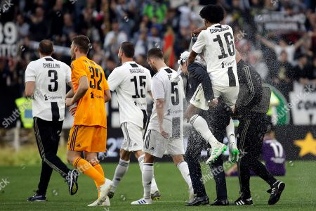 Juventus' Juan Cuadrado, right, sprays foam over Juventus coach Massimiliano Allegri at the end of a Serie A soccer match between Juventus and AC Fiorentina, at the Allianz stadium in Turin, Italy, . Juventus clinched a record-extending eighth successive Serie A title, with five matches to spare, after it defeated Fiorentina 2-1
