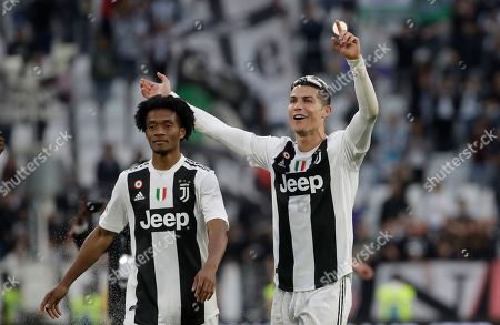 Juventus' Juan Cuadrado, left, and Cristiano Ronaldo celebrate at the end of a Serie A soccer match between Juventus and AC Fiorentina, at the Allianz stadium in Turin, Italy, . Juventus clinched a record-extending eighth successive Serie A title, with five matches to spare, after it defeated Fiorentina 2-1