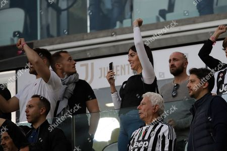 Juventus' Cristiano Ronaldo's girlfriend Georgina Rodriguez waves from the stands at the end of a Serie A soccer match between Juventus and AC Fiorentina, at the Allianz stadium in Turin, Italy, . Juventus clinched a record-extending eighth successive Serie A title, with five matches to spare, after it defeated Fiorentina 2-1