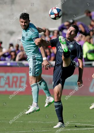 Felipe Martins, Sacha Kljestan. Orlando City's Sacha Kljestan, right, clears the ball away from Vancouver Whitecaps' Felipe Martins (8) during the second half of an MLS soccer match, in Orlando, Fla