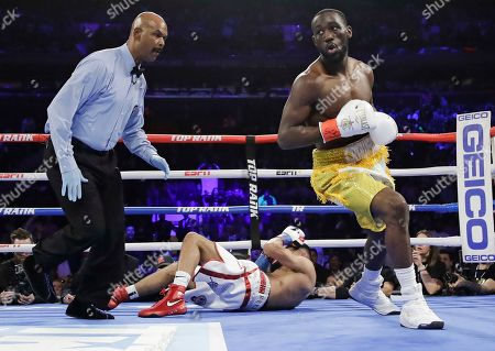 Terence Crawford, right, reacts after knocking down England's Amir Khan during the first round of a WBO world welterweight championship boxing match, in New York. Crawford won the fight