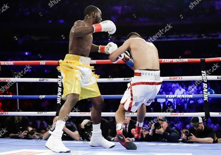 Terence Crawford, left, knocks down England's Amir Khan during the first round of a WBO world welterweight championship boxing match, in New York. Crawford won the fight