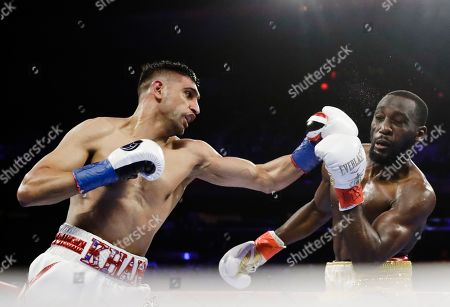 England's Amir Khan, left, punches Terence Crawford during the second round of a WBO world welterweight championship boxing match, in New York. Crawford won the fight