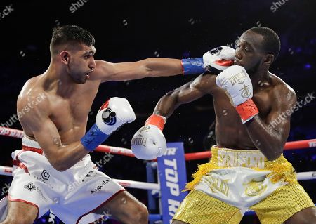 England's Amir Khan, left, punches Terence Crawford during the third round of a WBO world welterweight championship boxing match, in New York. Crawford won the fight