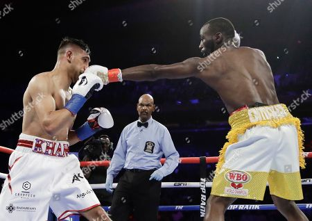 Terence Crawford, right, punches England's Amir Khan during the second round of a WBO world welterweight championship boxing match, in New York. Crawford won the fight
