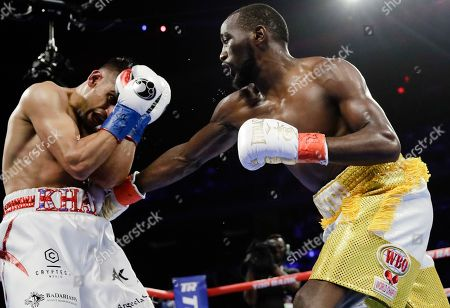 Terence Crawford, left, punches England's Amir Khan during the fourth round of a WBO world welterweight championship boxing match, in New York. Crawford won the fight