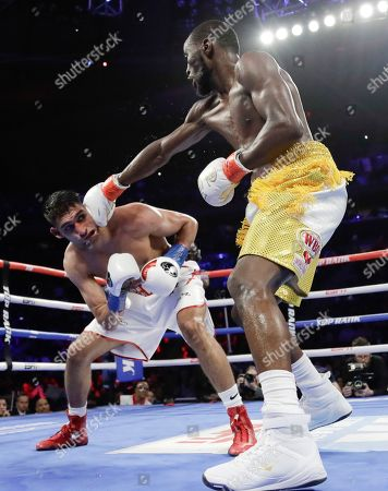 Terence Crawford, right, punches England's Amir Khan during the fifth round of a WBO world welterweight championship boxing match, in New York. Crawford won the fight when Kahn could no longer continue after a low blow in the sixth round