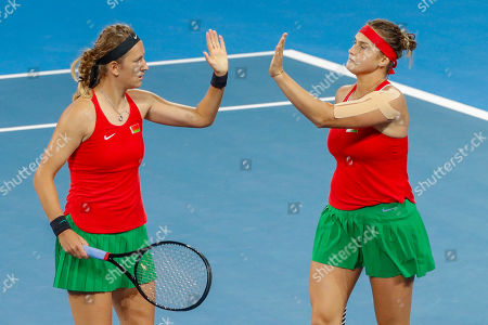 Stock Photo of Aryna Sabalenka (right) and Victoria Azarenka (left) of Belarus celebrate winning the second set against Sam Stosur and Ash Barty of Australia during the Fed Cup World Group semifinal between Australia and Belarus at Pat Rafter Arena in Brisbane, Australia, 21 April 2019.