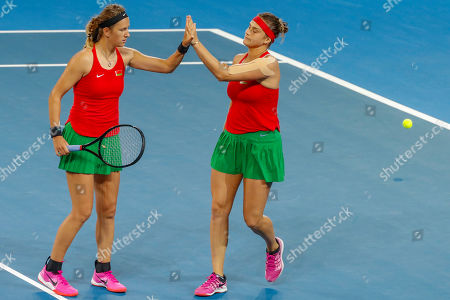 Stock Picture of Aryna Sabalenka (right) and Victoria Azarenka (left) of Belarus celebrate winning the second set against Sam Stosur and Ash Barty of Australia during the Fed Cup World Group semifinal between Australia and Belarus at Pat Rafter Arena in Brisbane, Australia, 21 April 2019.