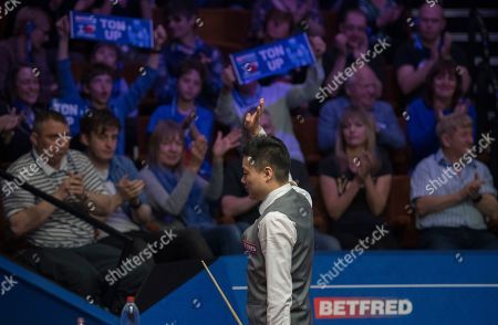 Ding Junhui of China waves to the crowd after winning his first round match