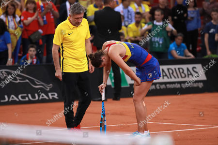 Irina-Camelia Begu (R) of Romania reacts  with her coach Florin Segarceanu (L) after being injured during her game against Pauline Parmentier of France during the Fed Cup World Group, Semi Final between France and Romania, in Rouen, France, 21 April 2019.