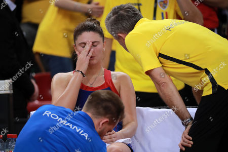 Irina-Camelia Begu (C) of Romania reacts as she receives medical treatment next to her coach Florin Segarceanu (R) after being injured during her game against Pauline Parmentier of France during the Fed Cup World Group, Semi Final between France and Romania, in Rouen, France, 21 April 2019.