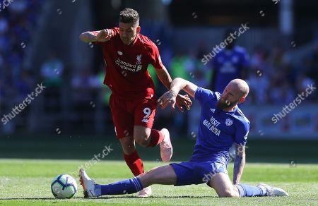 Roberto Firmino of Liverpool skips past Aron Gunnarsson of Cardiff City