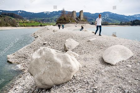 People walk on a strip of sand and stones leading to the island of Ogoz in the Lake Gruyere near Pont-en-Ogoz, canton Fribourg, Switzerland, 21 April 2019. A few weeks in spring, the Ile d'Ogoz is accessible by foot when the lake level is low enough, i.e. below 668 meters. At this time, the lake level is gradually lowered in anticipation of snowmelt from the surrounding mountains. On the island are a ruined castle and a church.
