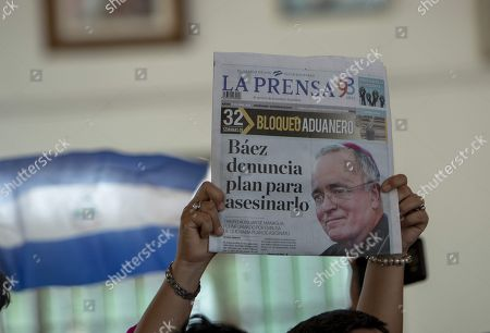 A woman raises a newspaper with the image of the auxiliary bishop of Managua, Monsignor Silvio Baez, where it written 'Baez denounces plan to assassinate him' during an Easter homily in Managua, Nicaragua, 21 April 2019. The Nicaraguan bishop Silvio Baez, a fierce critic of the government of Daniel Ortega in the context of the crisis that Nicaragua has been experiencing for a year and that has left hundreds dead, pleaded for always being on the side of the victims and defending life and human dignity.