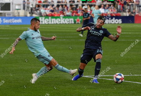 D.C. United Midfielder (10) Luciano Acosta crosses the ball in front of New York City FC Defender (22) Ronald Matarrita during an MLS soccer match between the D.C. United and the New York City Football Club at Audi Field in Washington DC