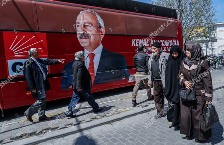 People walk in front of the picture of Turkey's main opposition Republican People's Party (CHP) leader Kemal Kilicdaroglu after a rally protesting the attack against Kilicdaroglu a day earlier, in Istanbul, Turkey, 22 April 2019. A group of people on 21 April attacked Kemal Kilicdaroglu before he was secured by police officers and guards during a soldier funeral in Cubuk district near Ankara.