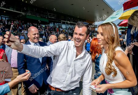A racegoer takes a picture with Una Healy, Judge for the Dunboyne Castle Most Stylish Lady competition