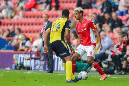 Charlton Athletic forward Lyle Taylor (9) and Scunthorpe United defender James Perch (14) during the EFL Sky Bet League 1 match between Charlton Athletic and Scunthorpe United at The Valley, London
