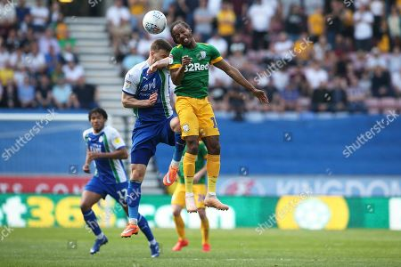 Wigan Athletic midfielder Lee Evans (36) and Preston North End midfielder Daniel Johnson (11) clash as they go for the high ball  during the EFL Sky Bet Championship match between Wigan Athletic and Preston North End at the DW Stadium, Wigan