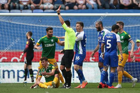 Referee Andrew Madley  shows Preston North End midfielder Ryan Ledson (18) (sitting) a straight red card during the EFL Sky Bet Championship match between Wigan Athletic and Preston North End at the DW Stadium, Wigan