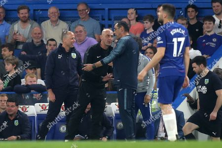 Chelsea Manager, Maurizio Sarri, speaks to the fourth official and gestures in the direction of the Burnley coaching staff as Ian Woan (Burnley Assistant Manager) chats with Gianfranco Zola (Chelsea Assistant Manager) in the background during Chelsea vs Burnley, Premier League Football at Stamford Bridge on 22nd April 2019
