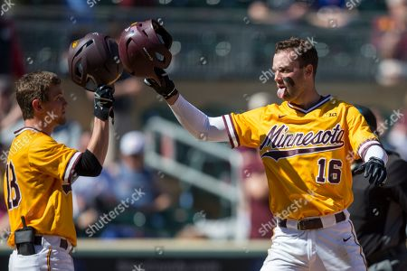 Minnesota's Easton Bertrand (16) celebrates a home run with teammate Riley Smith against Oklahoma during an NCAA college baseball game, in Minneapolis