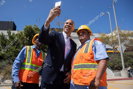 Democratic presidential candidate Sen. Cory Booker, center, takes a selfie with employees during his visit to the Hyperion Water Reclamation Plant, in the Playa del Rey section of Los Angeles